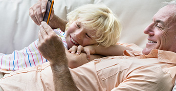 Grandfather and Grandson looking at cellphone