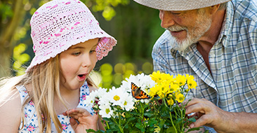 Grandaughter and Grandfather smelling flowers